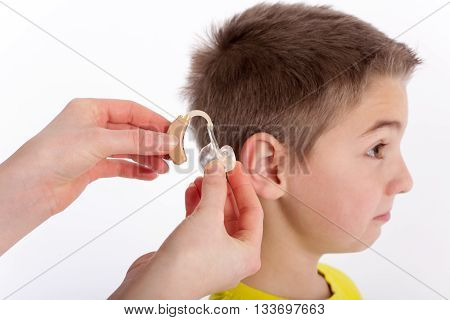 Audiologists inserting a hearing aid into a young boys ear. Focused on the hand and the hearing aid. poster