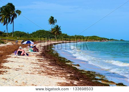 May 20, 2016 in Bahia Honda Key, FL:  Tourists relaxing on the white sand beach surrounded by Palm Trees, tropical plants, and the Atlantic Ocean taken at Bahia Honda Key, FL