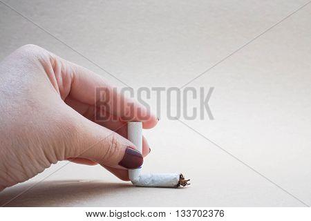 conceptual photo of smoking ban with human hand crash cigarrette