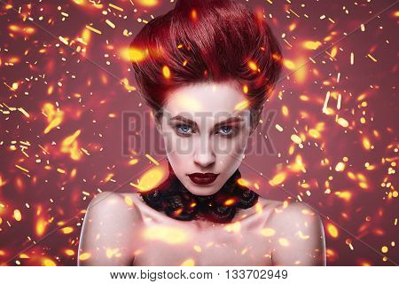 beauty stylish redhead woman with hairstyle and wearing necklace jewelry with falling fire sparkles feathers in studio on red background