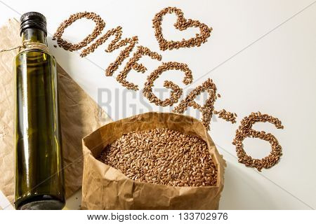 Flax seeds, linseed oil in the bottle on the light background.