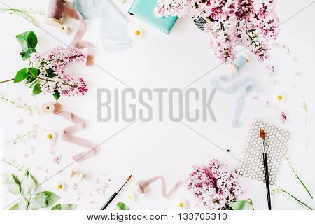 floral frame with lilac flower chamomile fresh branches and spool with blue and beige ribbon notebook isolated on white background. flat lay top view