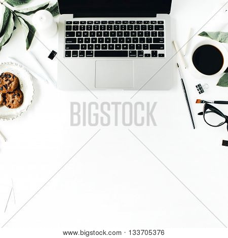 Workspace with laptop glasses cup of black coffee cookies on golden tray pencils paintbrushes and leaf. Flat lay composition for bloggers magazines social media and artists. Top view home office.