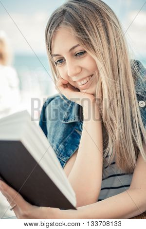 Beautiful Smiling Woman In Jeans Jacket Reads Book Summer Background