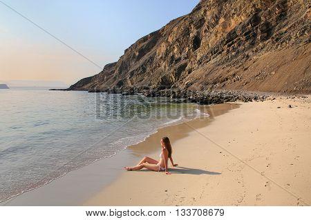Young Woman In Bikini Sitting At La Mina Beach In Paracas National Reserve, Peru
