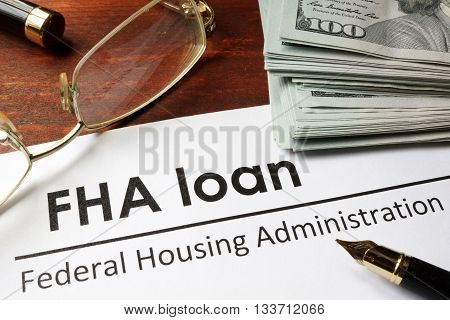 Paper with words fha loan on a wooden background.