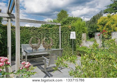 Appeltern The Netherlands July 22 2015: The Gardens of Appeltern is the inspiration garden park in the Netherlands. In this picture a garden with terrace and trendy garden furniture and white standing living room lamp.