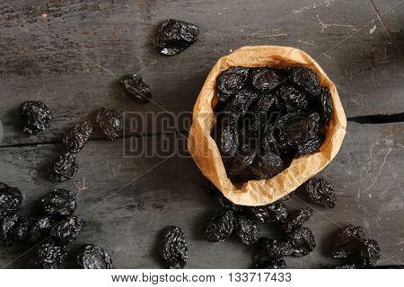 Raw organic prunes, dried plums on a dark background