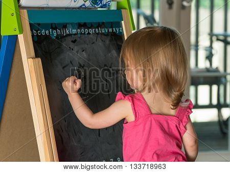 Young Baby Girl Drawing At Blackboard