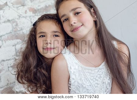 Two cute little sisters huddled together on a white background