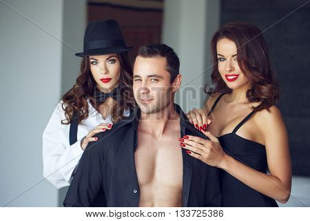Sexy macho man winking with wife and lover in luxury flat bigamy