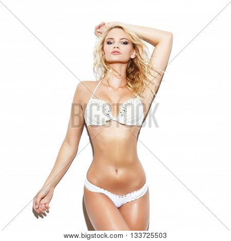 Sexy blonde caucasian woman in bikini posing at white wall