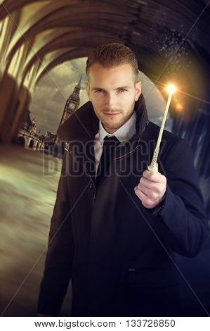 young wizard holding a magic wand in front of the city of london