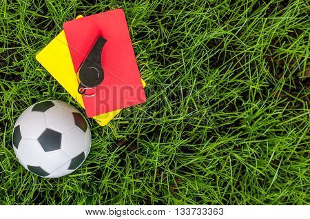Soccer referee outfit a yellow and red card with ball on lawn of stadium. Football background.
