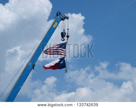 Dallas, USA, 10 June 2016. American Flag and Texas State Flag on Construction Crane is a long held tradition at construction sites. This one was at the construction companies home office in Dallas, 10 June 2016.