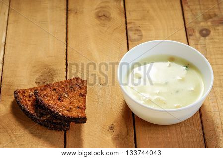 Creamed soup and sliced bread on a wooden table