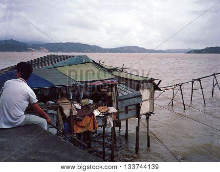 MACAU - CIRCA 1987: A man sits on a dike near a small house built on stilts over the ocean.