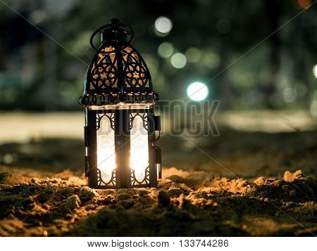 lighting with candle inside Lantern shining on sand floor playground children play with it in Ramadan night arabic style lantern also known Ramadan vintage lantern