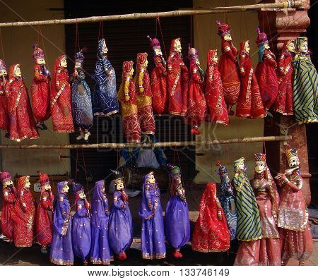 Indian handicraft of colorful puppets(Kathputhli-used to perform rajasthani folk songs and plays at fairs and festivals) attached to string on sale at a tourist shop in jaipur, Rajasthan, India.