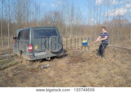 LENINGRAD REGION, RUSSIA - APRIL 16, 2016: The man tightens the rope for pulling out stuck in the mud UAZ-Patriot