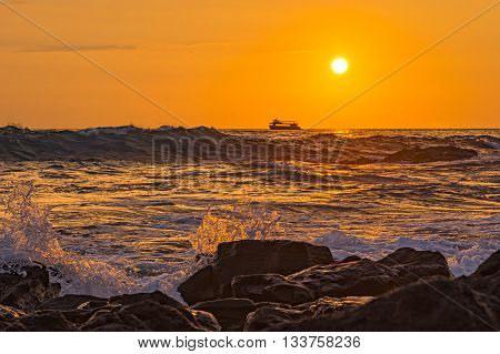 Ocean Surf crashes against the Shore at Sunset Kailua-Kona Big Island Hawaii USA