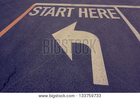 Start here word on road with turn left arrow