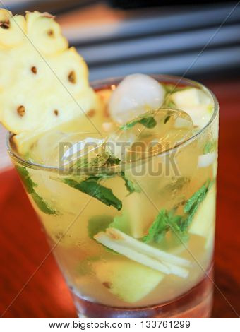Fresh Pineapple Mojito on wooden table close up