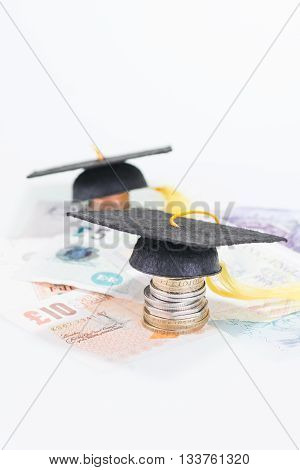 Mortarboards on stacked of coins and banknotes