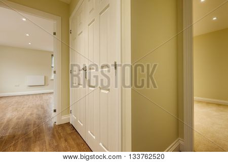 Apartment Hallway leading to two further rooms including large double door cupboard