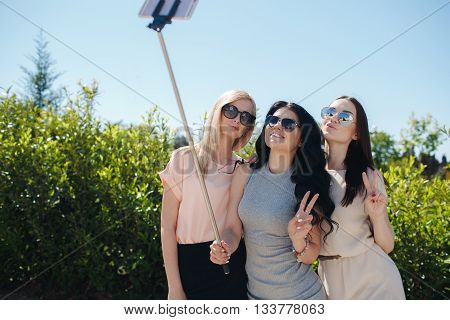 Three young girlfriend, brunette,blonde and girl with black long curly hair,nice smile,light makeup,wear jewelry,make selfi using monopod and smartphone,standing together outdoors in the Park on a background of green plants in the summer
