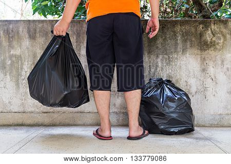 Low Section Of A Young Man Carrying Garbage Bag