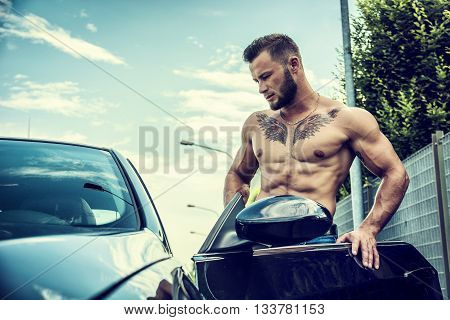Portrait of handsome bearded topless man with tattoo getting in beautiful car