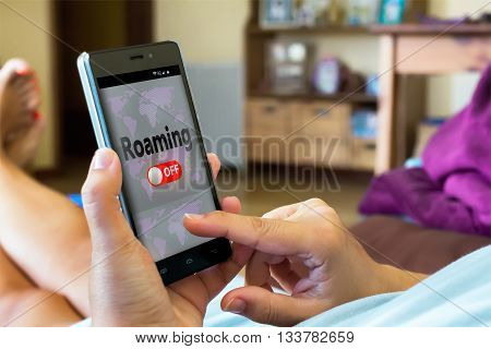 Close-up of woman switching off roaming on smartphone Shallow Depth of field