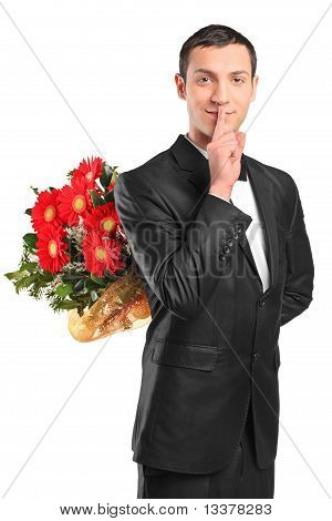 Handsome Male Hiding A Bouquet Of Flowers And Gesturing Silence