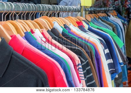 Front view of polo shirts on hanger. Colorful polo shirts in retail shop. Close up of polo shirts in retail shop