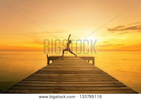 Yoga pose - Woman silhouette practicing yoga Warrior pose on sea bridge at sunset.Yoga near beach.