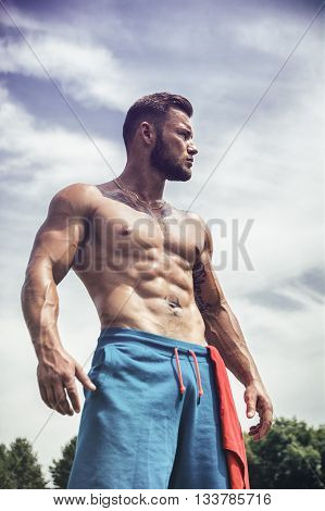 Tattooed sportsman with beard looking away in sunlight outdoor.Cloudy sky on background