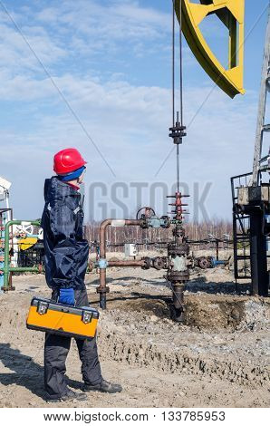Worker near wellhead with the tool box in his hand in the oilfield. Pumpjack background. Oil and gas concept.