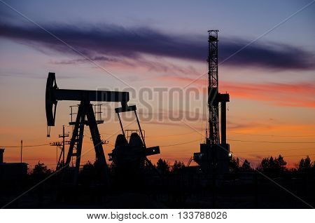 Pump jack and derrick silhouette during sunset on the oilfield. Oil and gas concept.