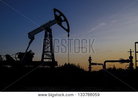 Pump jack and wellhead silhouettes during sunset on the oilfield. Oil and gas concept.