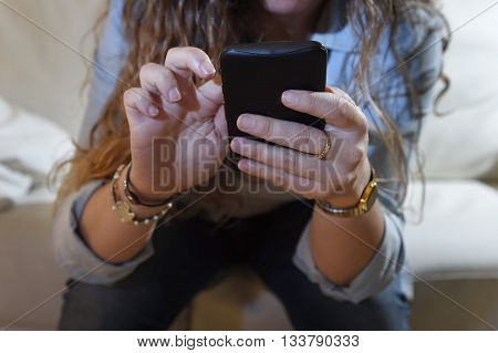 close up hands of woman holding mobile phone texting on social network at home couch in telephone addiction and internet overuse concept