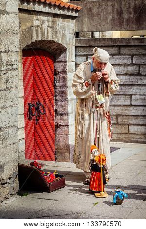 Tallinn Estonia - June 2 2016: Puppet master and string marionette doll in the Historical Center of Tallinn city. Tallinn Estonia.