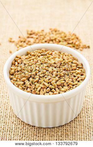 Fenugreek seeds in white bowl on sack background.