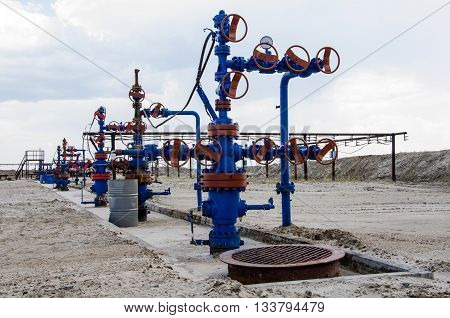 Group of wellheads and pipeline. Oilfield with sand ground. Oil and gas concept.