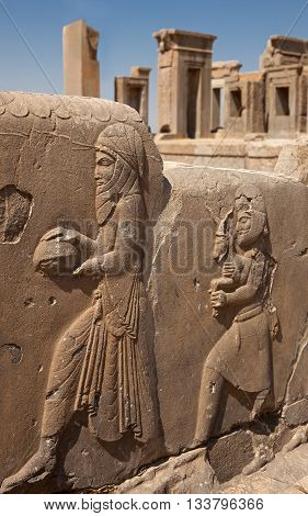 Embossed bas relief carvings of servants bringing gifts to the Achaemenian King on the sidewall of stairs in front of Tachara Palace or Palace of Darius in Persepolis of Shiraz.