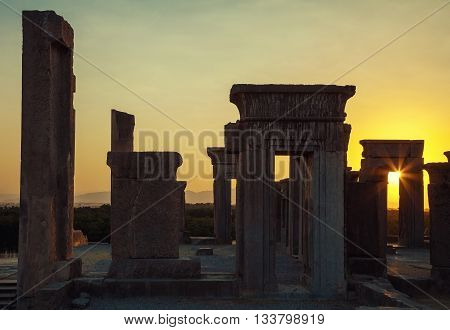 Beautiful Sunset with warm orange glow behind ruins of Tachara Palace or Palace of Darius from Achaemenid Empire in Persepolis of Shiraz. poster