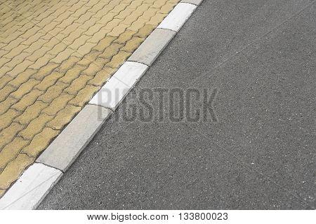 Striped border between the sidewalk and the asphalt road.