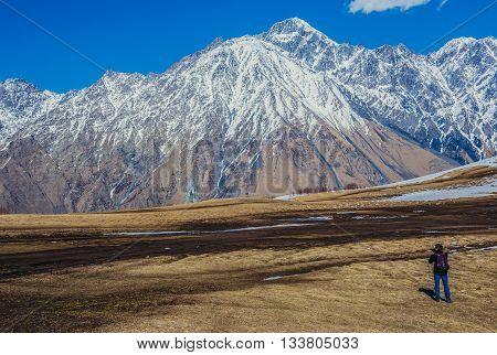 Gergeti Georgia - April 25 2015. Man takes photo of Caucasus Mountains near famous Holy Trinity Church. Mount Shani on background
