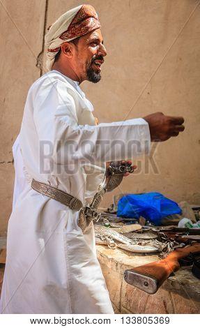 NIZWA, OMAN, MAY 27, 2016: An Omani man in a traditional outfit wearing khanjar at the gun market in Nizwa, Oman