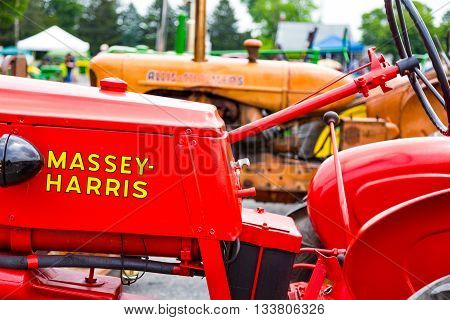 East Petersburg PA -June 1 2016: A bright red restored Massey Harris tractor on dislay a the Roots Auction annual tractor show.
